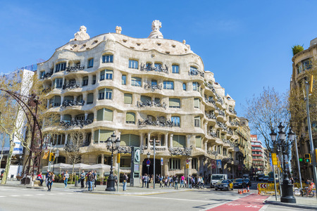 modernist: Barcelona, Spain - March 27, 2015: Street traffic and people in front of the famous Casa Mila or La Pedrera building.  View of Casa Mila, better known as La Pedrera, designed by Antoni Gaudi. It is the best exponent in modernist architecture.