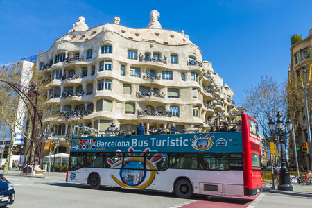 Barcelona, Spain - March 27, 2015: Tour bus in front of the famous Casa Mila or La Pedrera building.  View of Casa Mila, better known as La Pedrera, designed by Antoni Gaudi. It is the best exponent in modernist architecture.
