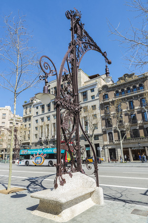 modernist: Barcelona, Spain - March 27, 2015: Bench and lamppost Modernist style one-piece built in 1906 and recently restored on the Passeig de Gracia. The bench is made with a technique called trencadis. In the background, a tourist bus passes