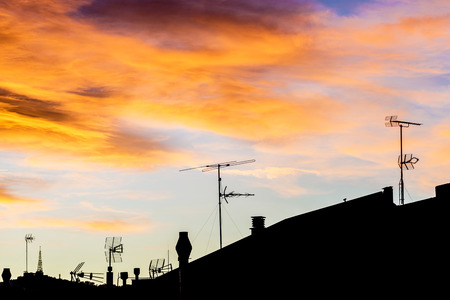 backlit: Silhouettes of antennas backlit at sunset with colorful sky clouds Stock Photo
