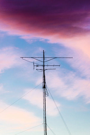 backlit: Silhouette of antenna backlit at sunset with colorful sky clouds Stock Photo