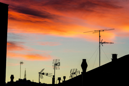 backlit: Silhouettes of antennas and chimneys backlit at sunset with colorful sky clouds