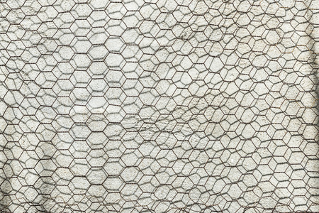 metal grate: Metal grate as hexagons on a concrete wall Stock Photo