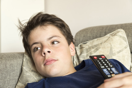 stretched: Young boy with TV remote control watching TV on the couch stretched