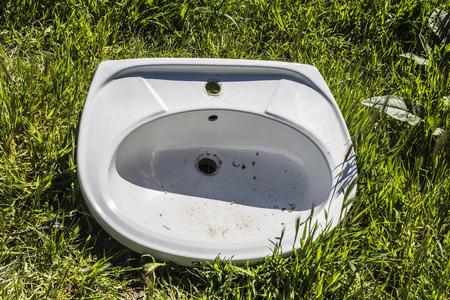 washbasin: Broken washbasin pulled on the grass Stock Photo