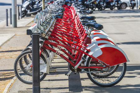 A row of rental bikes in their docking stands in downtown Barcelona, Catalonia, Spain