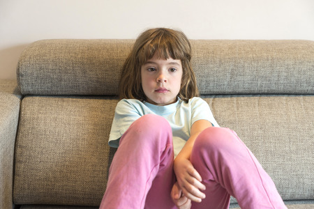 absorbed: Little girl watching TV sitting on the couch Stock Photo