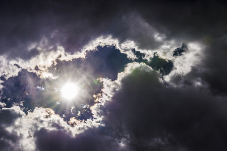 beaming: Dramatic sky with the sun beaming among the clouds. Natural background. Stock Photo