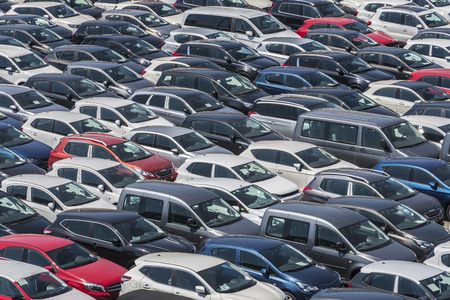New cars parked in a row in the port of Barcelona, Catalonia, Spain. They are waiting to be shipped.