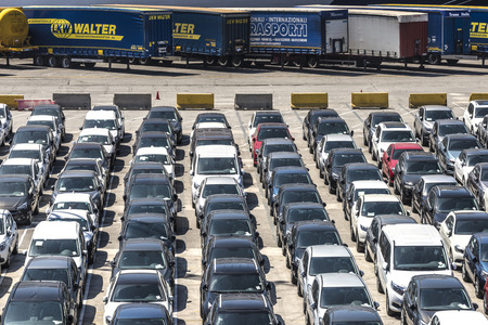 shipped: Barcelona, Spain - May 2, 2015: New cars parked in a row in the port of Barcelona. They are waiting to be shipped. In the background is parked trucks and containers.