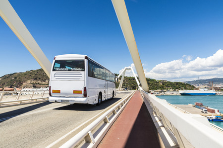 White bus circulating on a drawbridge over the port of Barcelona, Catalonia, Spain