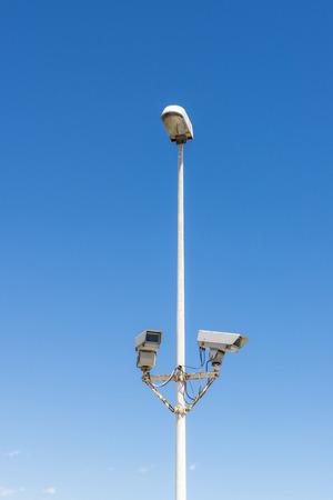 cielo despejado: Dos c�maras de seguridad conectadas a un poste de luz contra el cielo azul