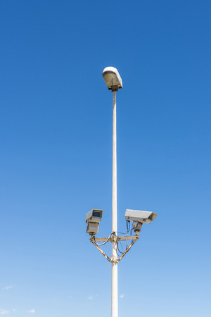 vcr: Two security cameras attached to a lamppost against blue sky