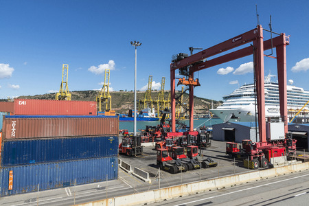 overhead crane: Barcelona, Spain - May 23, 2014: Cranes in the container terminal in the port of Barcelona with a cargo ship waiting next to cruise terminal
