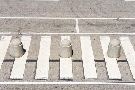 no pase: Alta vista de un paso de peatones con tres bolardos