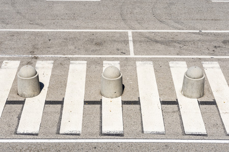 dividing lines: High view of a pedestrian crossing with three bollards