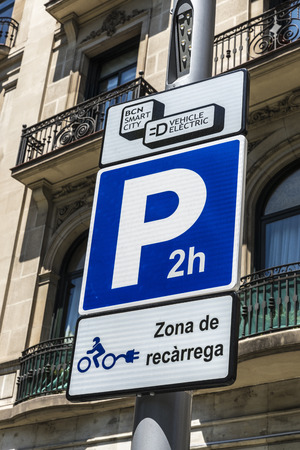 parking station: Barcelona, Spain - May 26, 2015: Signal indicating an electric charging station for electric motorbikes and cars with parking for two hours