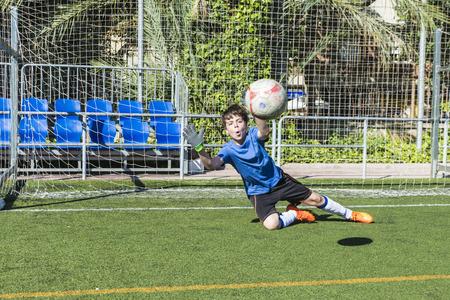 portero futbol: Portero de f�tbol joven que estira para detener una bola