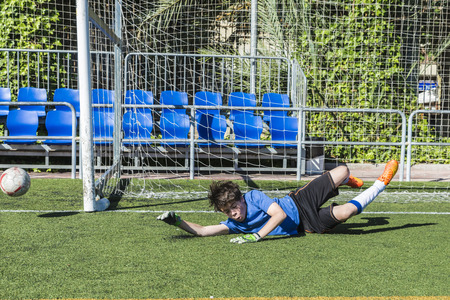 ball stretching: Young football goalkeeper stretching to stop a ball