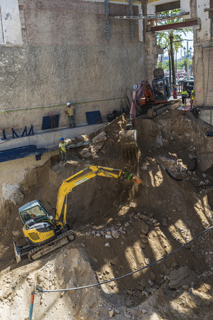 bulldozers: Barcelona, Spain - June 4, 2015: Construction of a building keeping the old facade through a system of beams. The workers and their bulldozers are doing the foundations of the new building Editorial
