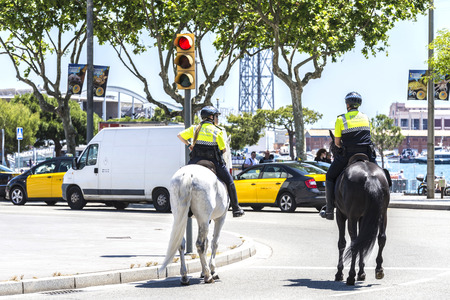ramblas: Barcelona, Spain - April 21, 2015: City police on horseback in Ramblas. This police force is called Guardia Urbana de Barcelona and one of its functions is to control the traffic in the city
