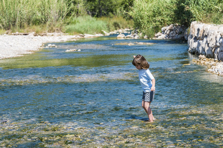 Little girl crossing a river full of stones carefully and teetering in Spain