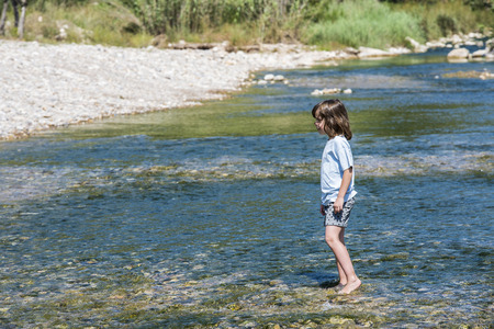 Little girl crossing a river full of stones carefully in Spain photo