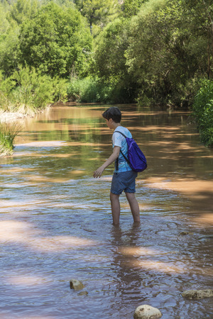 Boy crossing a river full of stones with care and teetering in Spain