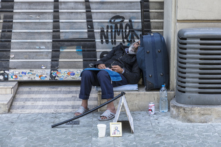 tramp: Barcelona, Spain - May 26, 2015: Tramp sleeping at the gates of a closed trade