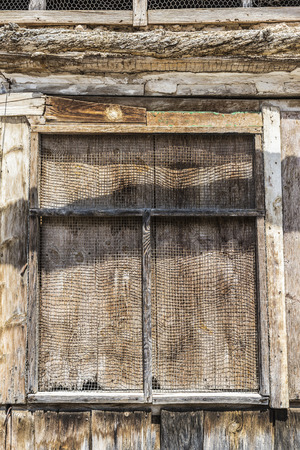 metal grate: Old wooden window covered with a metal grate in Spain