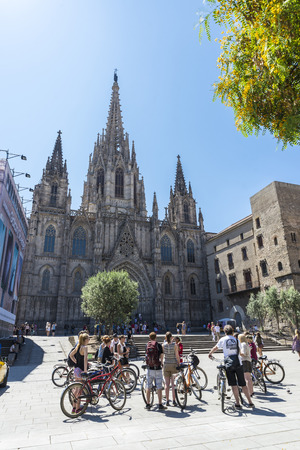 samsung galaxy: Barcelona, Spain - June 17, 2015: Cycling tour group with a guide in front of the Barcelona cathedral. In the background, a building restoration is a tarp covering it with an announcement of Samsung Galaxy S6