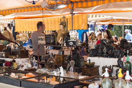 predominate: Barcelona, Spain - June 17, 2015: Flea market located in front of Barcelona Cathedral. In the picture you see a seller and customers in a place where they predominate the old cameras