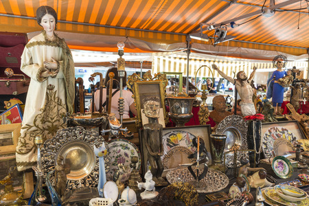 Barcelona, Spain - June 17, 2015: Flea market located in front of Barcelona Cathedral. In the picture you see a seller and customers in a place where they predominate religious figures of Jesus Christ and saints