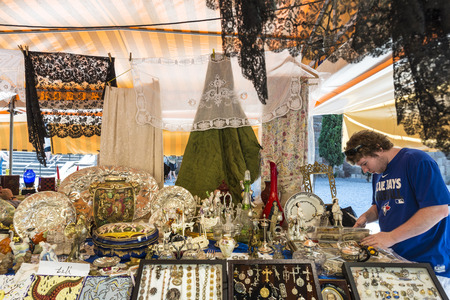 Barcelona, Spain - June 17, 2015: Flea market located in front of Barcelona Cathedral. In the image a customer looking for something interesting in a place where they predominate and silver metal plates, vases and mantillas Editorial