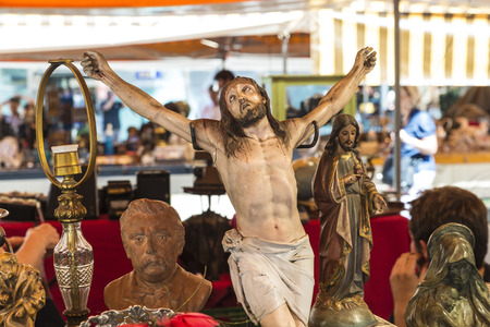 antiquities: Barcelona, Spain - June 17, 2015: Flea market located in front of Barcelona Cathedral. In the picture you see a seller and customers in a place where they predominate religious figures of Jesus Christ and saints