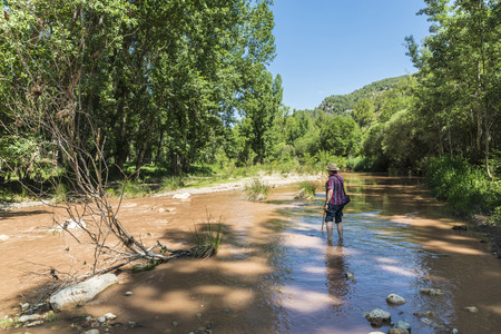 cane creek: Montanejos, Spain - May 31, 2015: Man crossing a river full of stones with care and teetering