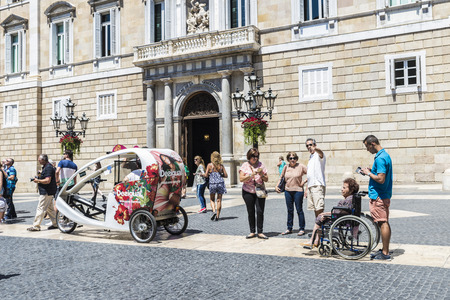 generalitat: Barcelona,Spain - June 17, 2015: People walking and a tricycle with Desigual advertising in Sant Jaume square, in front of the facade of Generalitat of Catalonia