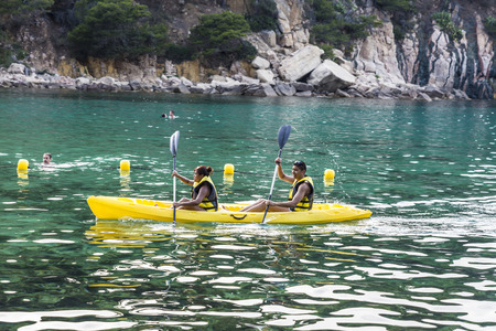 beaches of spain: Girona, Spain - July 1, 2015: Young couple paddling in kayak on sea in Costa Brava, Catalonia, Spain Editorial
