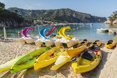 ocean kayak: Girona, Espa�a - Junio ??30, 2015: kayaks y canoas y barcas de pedales con diapositivas sobre la playa de Aiguablava, en la Costa Brava, Catalu�a, Espa�a Editorial