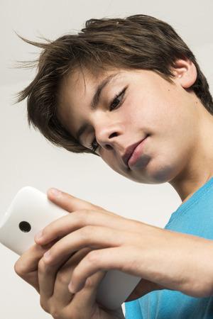 Ragazzo toccando un telefono cellulare isolato su sfondo bianco