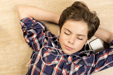 arms behind head: Portrait of a boy listening to music with headphones stretched on a wooden floor at home with arms behind his head