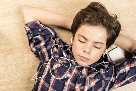 stretched: Portrait of a boy listening to music with headphones stretched on a wooden floor at home with arms behind his head