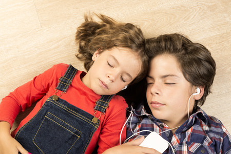 stretched: Portrait of children listening to music with headphones stretched on a parquet floor at home