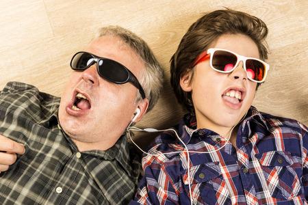 padres: Padre e hijo escuchando música juntos con auriculares estiran en un piso de madera en casa