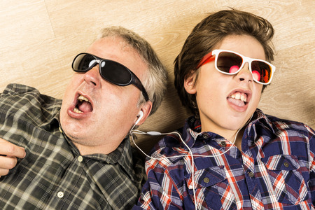 Father and son listening to music together with headphones stretched on a wooden floor at home
