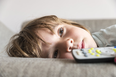 Little girl watching TV on the couch stretched Stock fotó