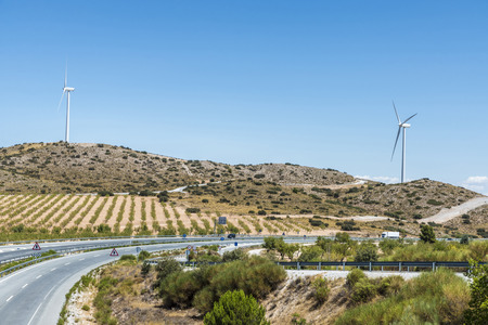 olive groves: Highway through Andalusia between olive groves and a wind farm in Spain