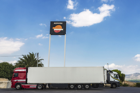 Valencia, Spain - August 18, 2015: Repsol logo trimmed against the sky with two trucks parked. Repsol is a Spanish multinational oil and gas company based in Madrid. Editorial
