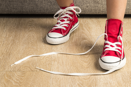 Little girl wearing a pair of red sneakers at home. A sneaker is untied Stock Photo