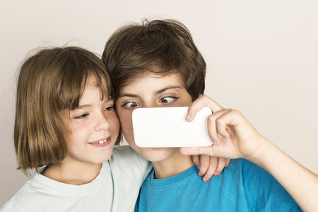 squint: Happy child doing a squint and taking a selfie with a smartphone at home isolated on white background Stock Photo